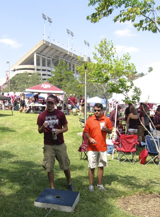 Cornhole competition between Gator Ryan and Aggie fan photo by Kathy Miller