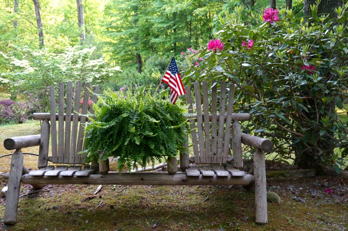 Mountain bench with fern and American flag photo by Kathy Miller