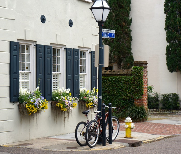 Window Boxes with pop of yellow and bikes photo by Kathy Miller