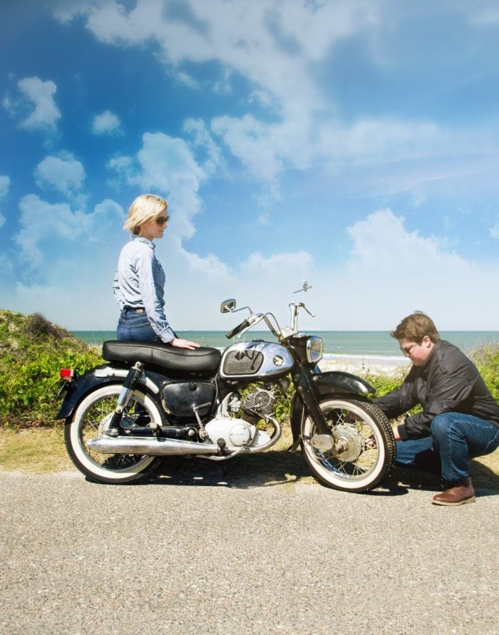 Mike checks tires on 1965 Honda Dream motorcycle while Gloria looks on photo by Susan Scarborough