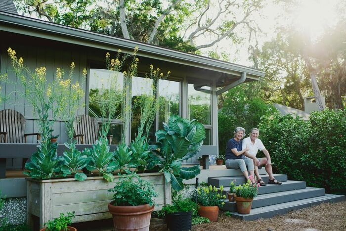 Paula and Bronson Lamb on porch with collard greens and tomato plants photo by Page Tehan