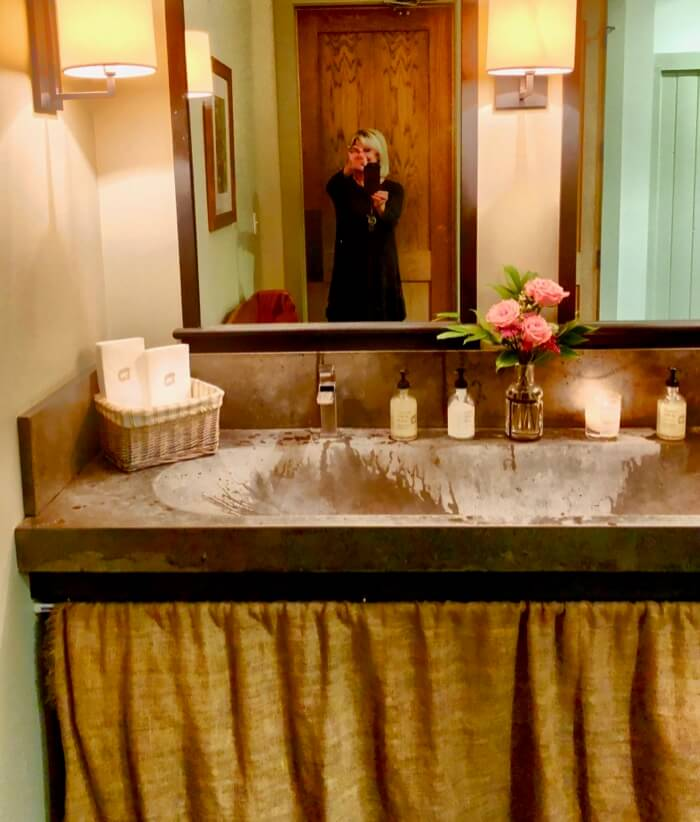 Kathy and the skirted sink at Canyon Kitchen bathroom photo by Kathy Miller