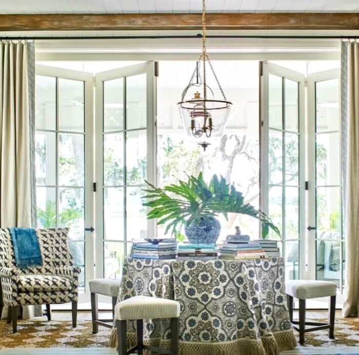 Table with books in Living room doors open to view Southern Living 2019 Idea House
