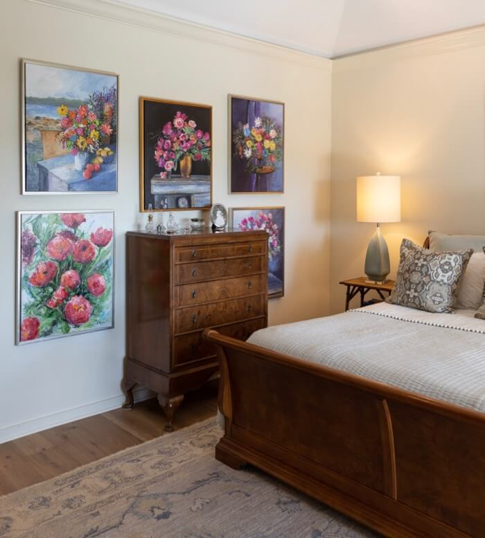 Main bedroom with Kathy Miller original flower paintings photo by Lynn Tennille