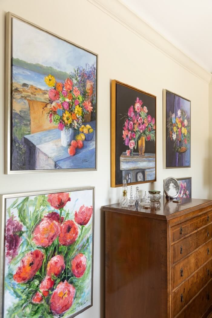 Kathy's flower paintings with antique chest and perfume bottle collection