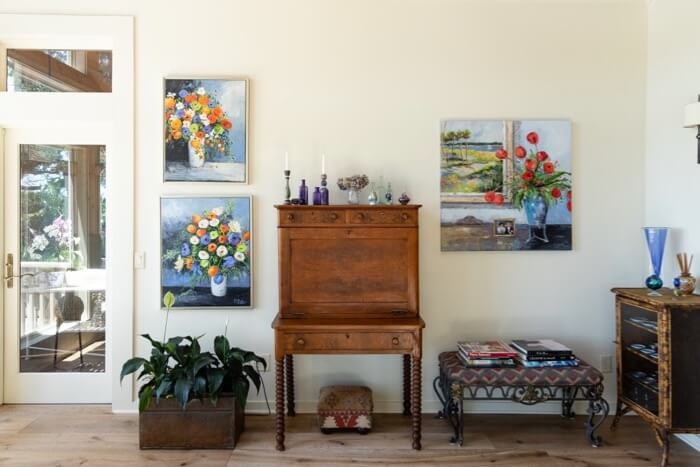 Sunroom with antiques and bright Kathy Miller original floral paintings photo by Lynn Tennille