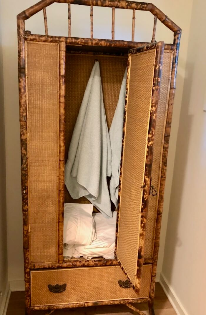 Antique armoire with towels and bed linens photo by Kathy Miller