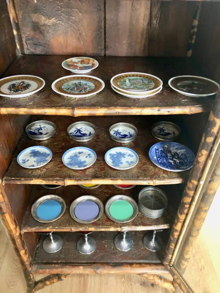 Old coaster collection in antique bamboo cabinet photo by Kathy Miller