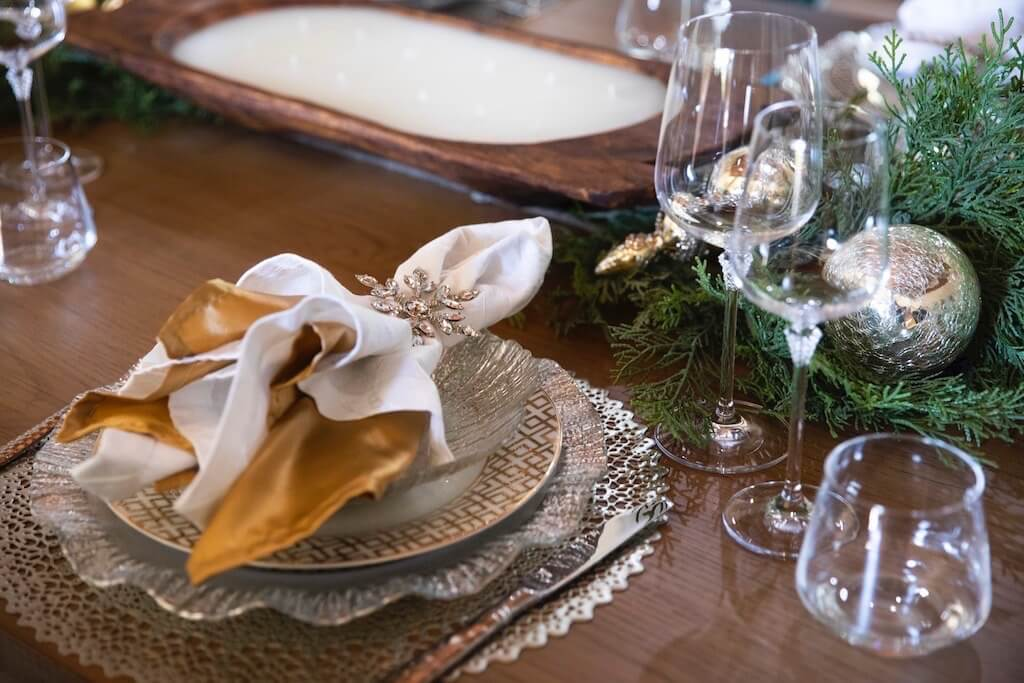 tablescape with gold, silver, cyrstal and greenery photo by Clay Greenhaw