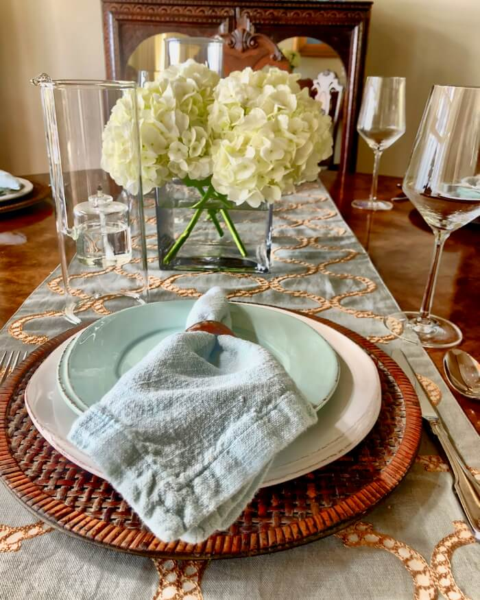Table setting with aqua and gold runner setting the tone with shell napkin rings photo by Kathy Miller